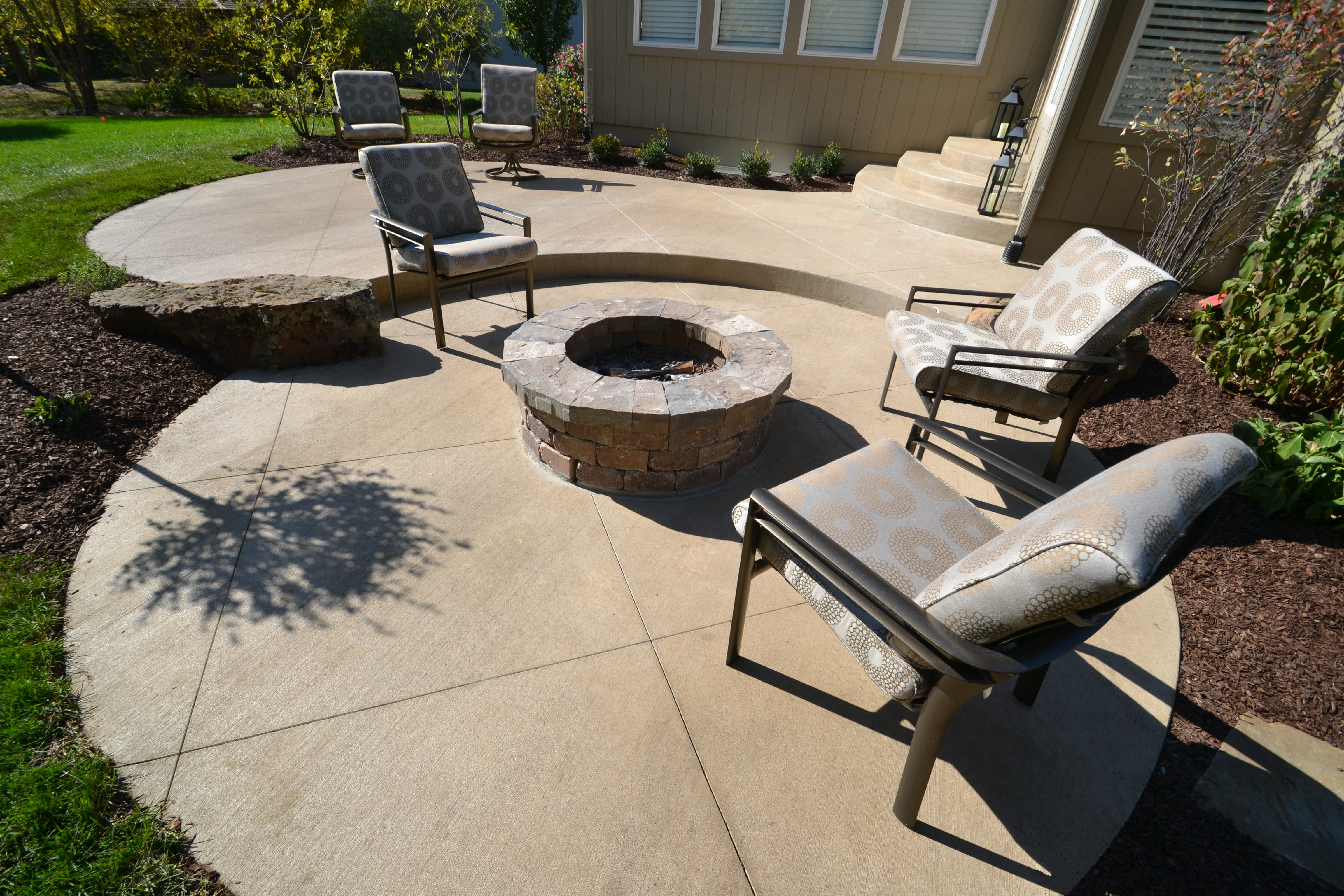 A round patio with a firepit made with custom concrete that you can get from Aesthetic Concrete Designs.