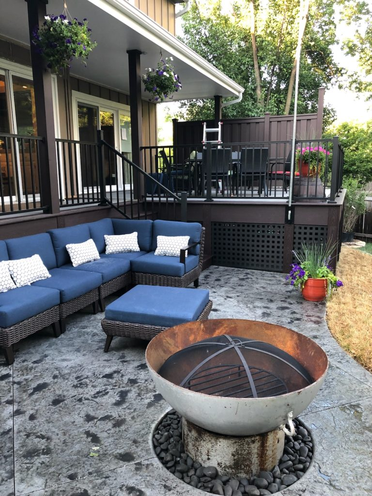 A concrete patio with chairs and a fire pit created by Aesthetic Concrete Designs.