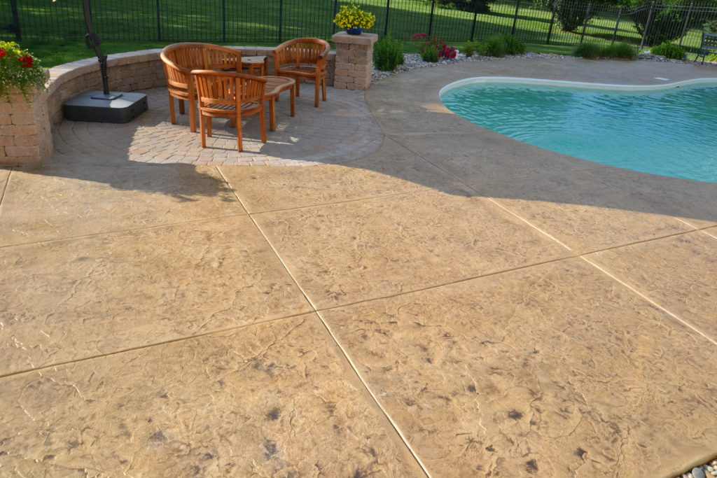 A stamped concrete pool deck featuring beige textured concrete from Aesthetic Concrete Designs.