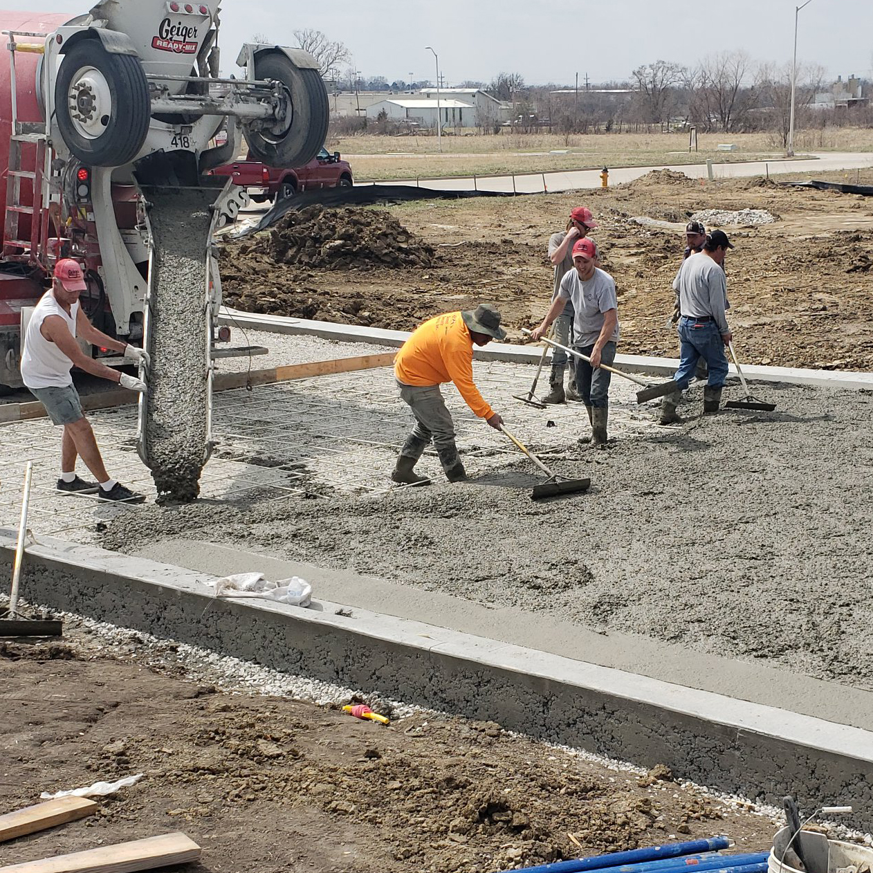 Workers installing concrete on a project by Aesthetic Concrete Designs for a custom patio or pool deck.