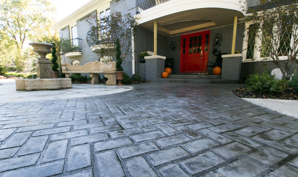 Custom stamped concrete that looks like a brick patio created by Aesthetic Concrete Designs