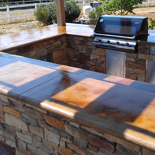 A custom outdoor kitchen featuring custom concrete countertops and a stone base by Aesthetic Concrete Designs.