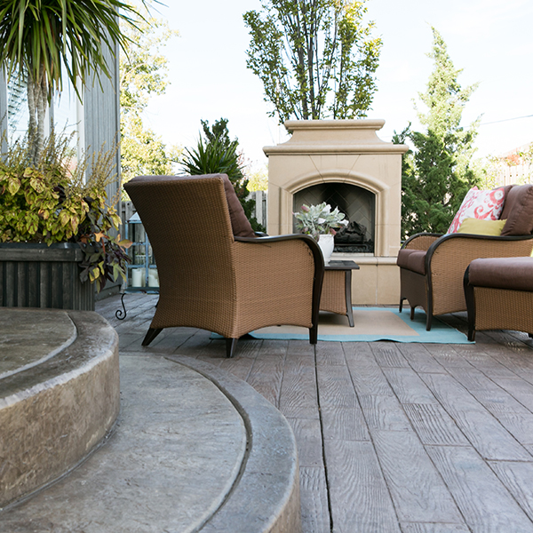 An outdoor fireplace with chairs on a concrete patio custom designed by Aesthetic Concrete Designs.