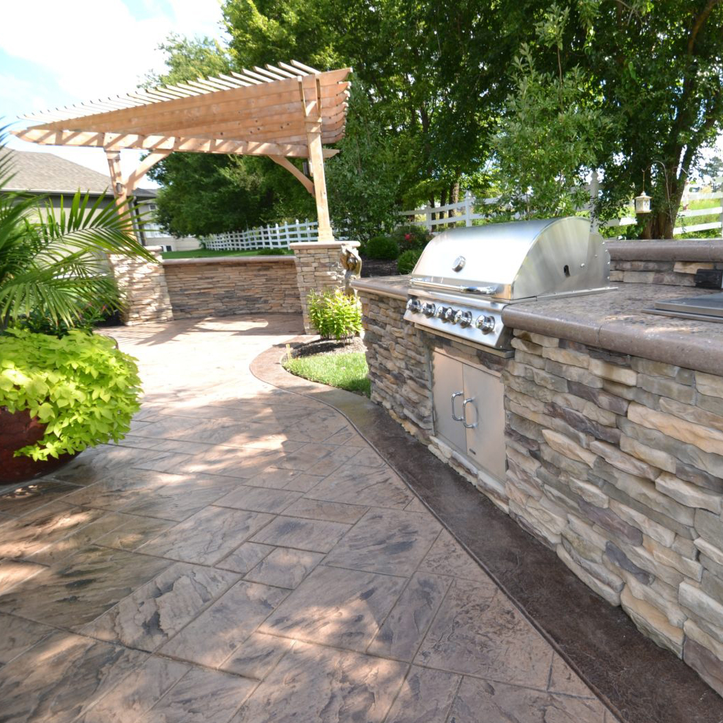 An outdoor kitchen featuring stamped concrete patio and custom concrete countertops by Aesthetic Concrete Designs.