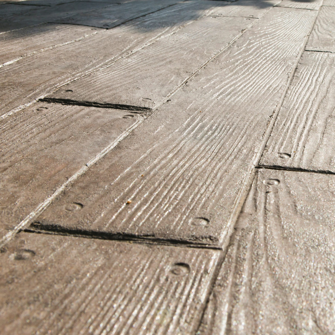 Stamped concrete that looks like wood planks is just one example of the concrete design services available from Aesthetic Concrete Designs.