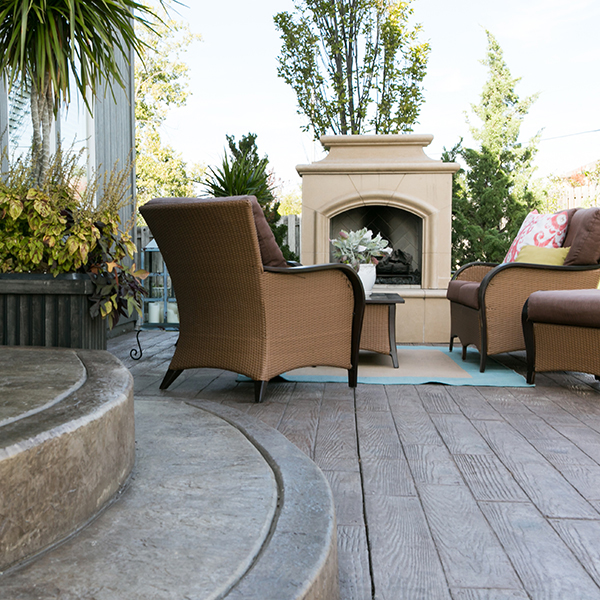 A concrete outdoor living area with a fireplace, chairs, and a stamped concrete patio by Aesthetic Concrete Designs.