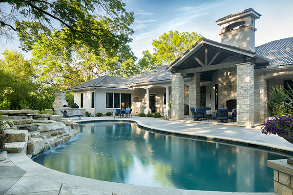 A custom concrete pool deck and patio with a decorative waterfall by Aesthetic Concrete Designs.